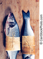 Sea bass fish raw on the wooden background
