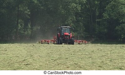 Tractor in hayland, shakes out and loosens hay - on camera -...