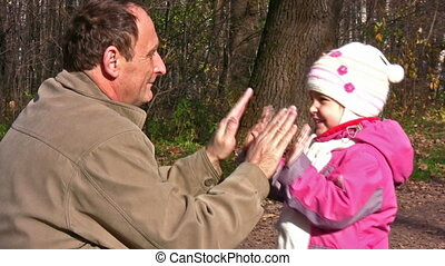 senior with little girl in autumn park play by hands -...