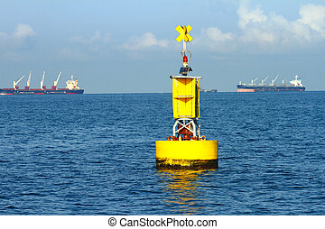 Floating yellow navigational buoy on blue sea