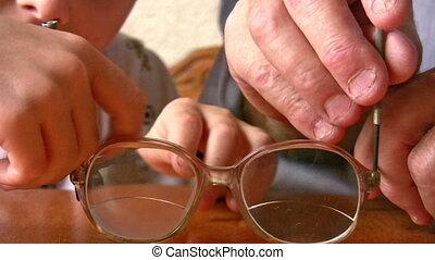 hands child with senior repair glasses
