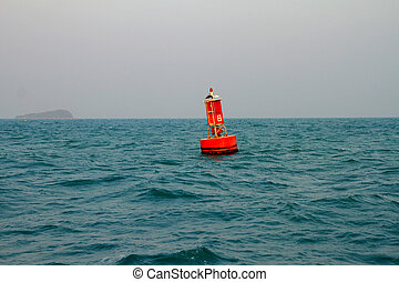 Floating red navigational buoy on blue sea.