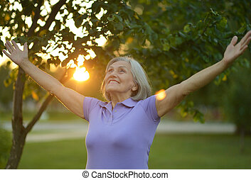 Woman stretching her hands up at sunset