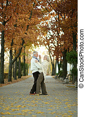 Mature couple dancing in park - Mature couple dancing in the...