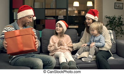Christmas Miracles - Festive family resting on sofa, father...