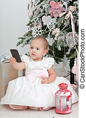 Little girl with the mobile phone sits near a Christmas...