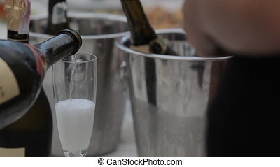 Sommelier pours a glass of champagne in posh restaurant -...