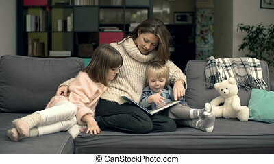 Reading Together - Family of three cuddling on couch and...
