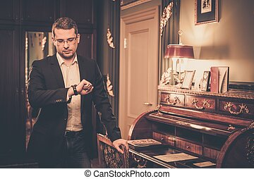 Middle-aged man looking at his wrist watch in luxury vintage...