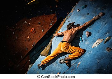 Muscular man practicing rock-climbing on a rock wall indoors...