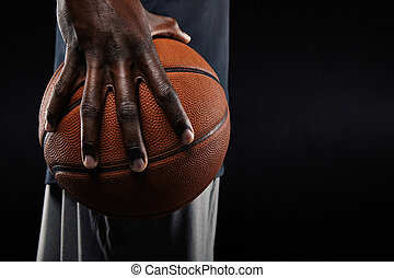 Hand of basketball player holding a ball - Close-up of a...