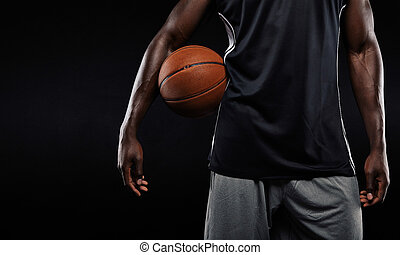 Afro american basketball player holding a ball - Cropped...