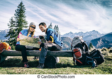 Couple hikers with map in mountains - Man and woman hikers...