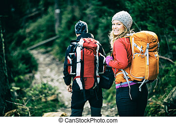 Couple hikers walking in mountains - Man and woman hikers...