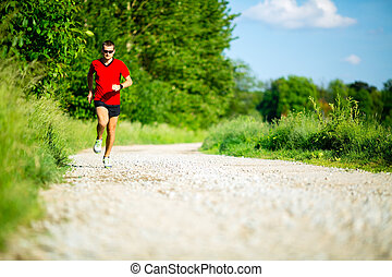 Man running on country road - Man runner running on country...