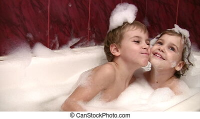 little girl with brother in bath