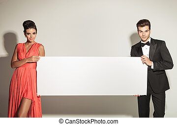 Fashion man and woman holding a blank board. - Fashion man...