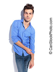 Attractive young fashion man pulling his sleeve.