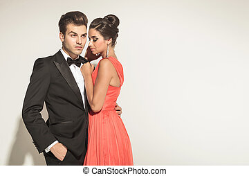 Picture of a young elegant couple posing, the man is looking...