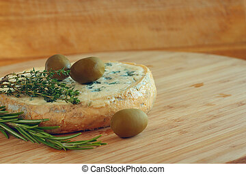 Cheese and Olives composition on wooden table
