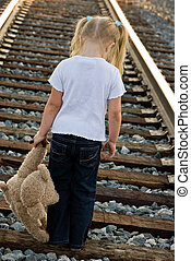So Sad - Little girl with teddy bear on railroad tracks.