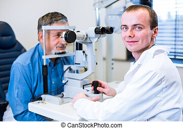 Optometry concept - senior man having his eyes examined by...