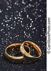 Two rings - Two golden rings on black glitter background