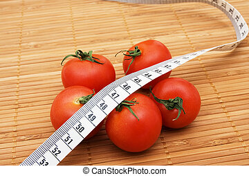 Weight Loss - Five ripe tomatoes with measuring tape sitting...