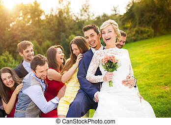 Newlyweds with guest posing in park - Portrait of newlywed...