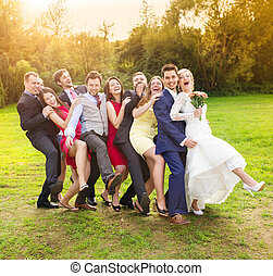 Newlyweds with guest posing in park - Full length portrait...