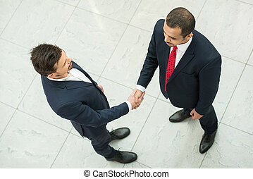 Business partners are shaking hands as a symbol of unity,...