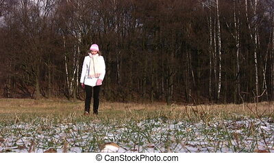 Woman walks in wood on first snow.