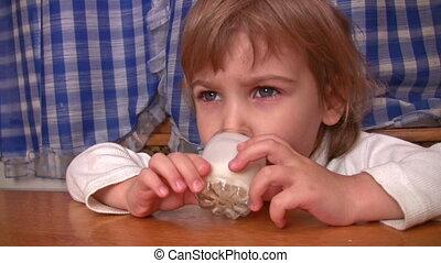 Little girl drinks kefir.