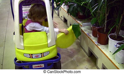 Little girl leaves shopping cart car near plants