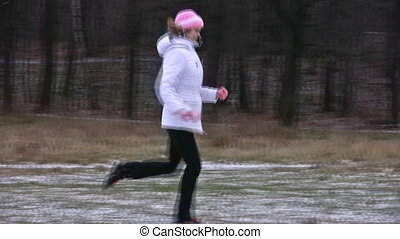 Woman running in wood with first snow.