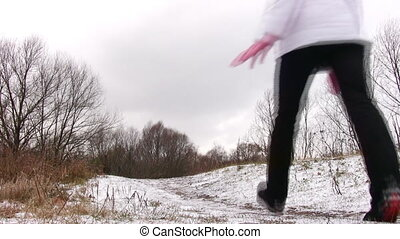 Woman running from camera like Buratino on first snow way.