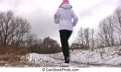Woman running from camera on first snow way.