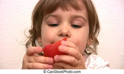 Little girl eats tomato