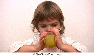 Little girl drinks juice