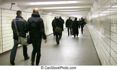 Behind going people in subway corridor