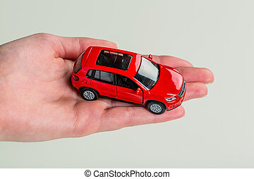 hand holding model of a car - a hand holding a model car....