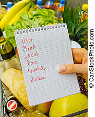 shopping list in the supermarket (german) - a woman holding...