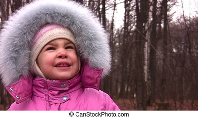 little girl with fur hood in park