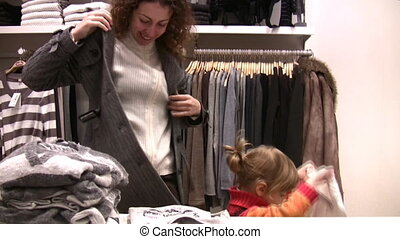 mother with little girl try fit clothes in shop - Mother...