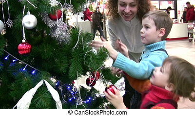 mother with children watching christmas tree in shop -...