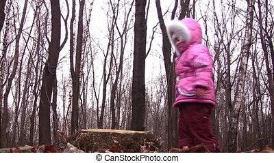 little girl jump from stub in winter park - Little girl jump...
