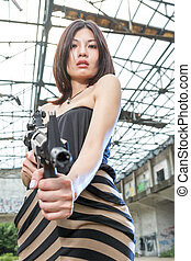 Asian woman with a gun in ruins - Chinese woman with...