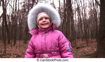 walking little girl in winter park to camera - Walking...