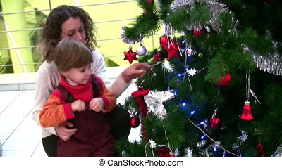 mother with little girl watching christmas tree in shop -...