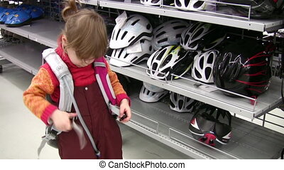 little girl with knapsack in shop, bicycle helmets - Little...